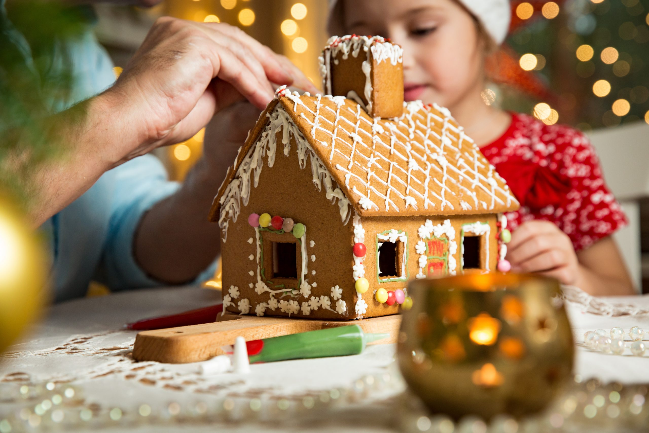 Father and adorable daughter in red hat building gingerbread house